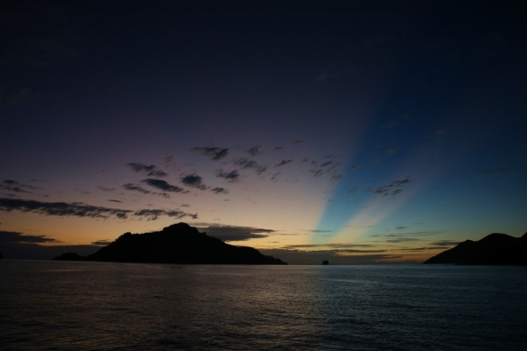 Sunbeams over Monu Island at sunset.